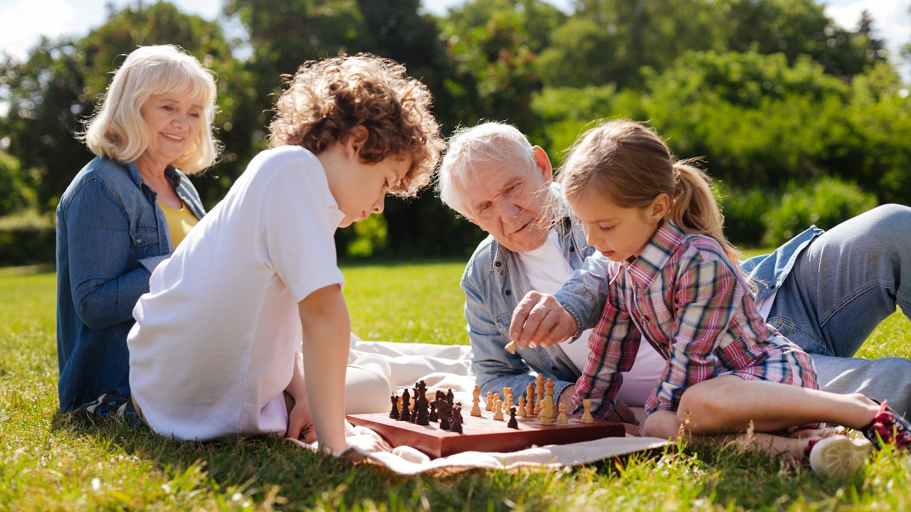 Family playing chess outside on the lawn; image used for HSBC Philippines Important Notice page